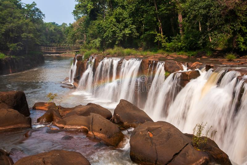 Gently rainbow over tropical waterfall. Tad Pha Suam waterfall in rainy season. Beautiful sandstone and gently waters falling off. The cliff, bamboo bridge royalty free stock image
