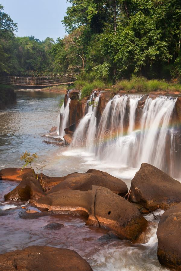 Gently rainbow over tropical waterfall. Tad Pha Suam waterfall in rainy season. Beautiful sandstone and gently waters falling off. The cliff, bamboo bridge stock photos