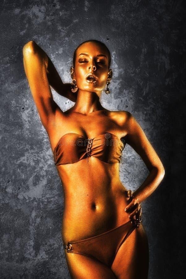 genuß Glatte Frau mit goldener Körper-Kunst glamor Auf dem Hintergrund der grauen Wand stockfotografie