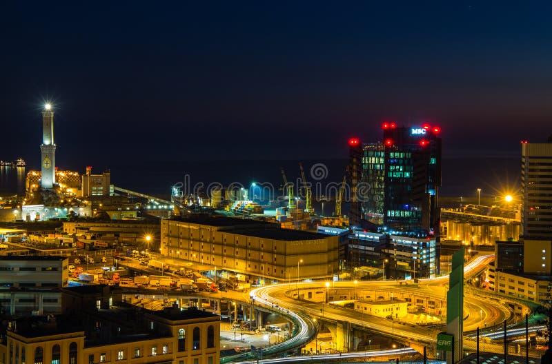 Genua, Italië, industriezone dichtbij de haven met Lanterna en commerciële wolkenkrabbers bij nacht royalty-vrije stock foto