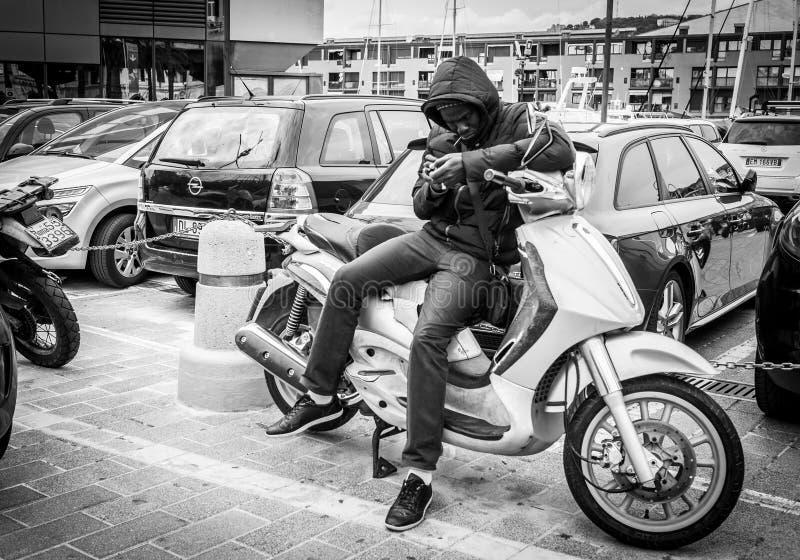 Genua Italien - April 21, 2016: Afrikansk man prata att använda royaltyfria foton