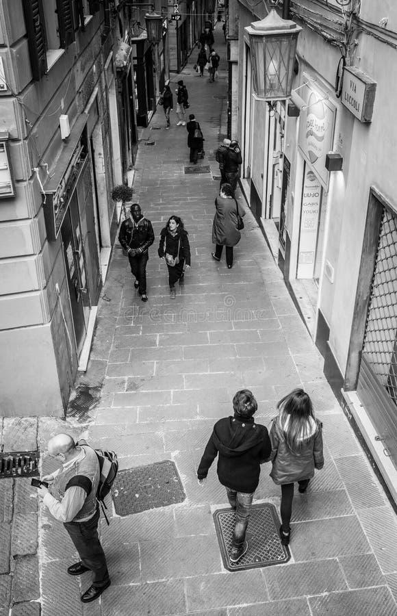 Genua Italien - April 21, 2016: Italienska förbipasserande som waling vid smalt royaltyfria bilder