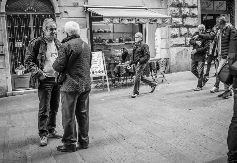 Genua Italien - April 21, 2016: Två män som möts på den ital gamla handeln royaltyfri foto