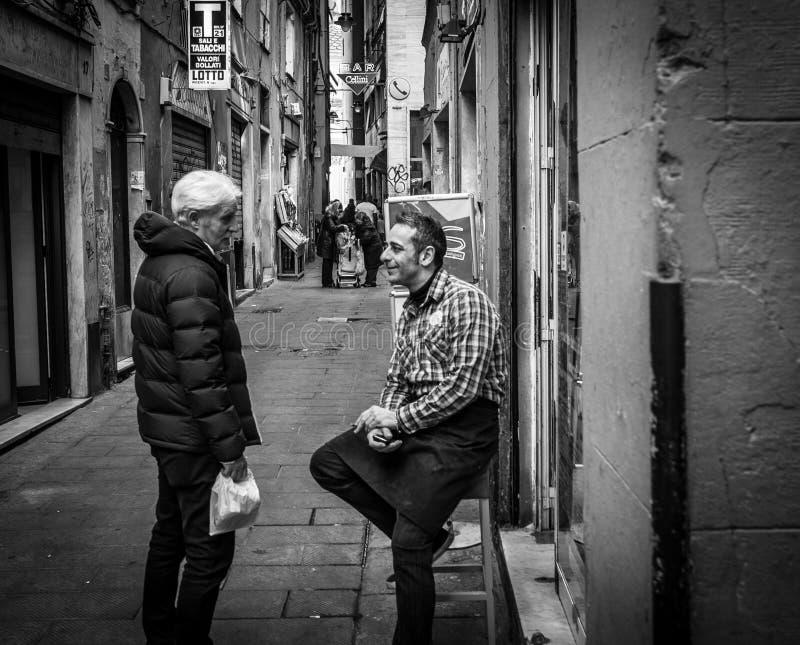 Genua Italien - April 21, 2016: Två män som möts på den ital gamla handeln royaltyfria bilder