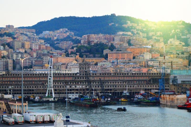 Genua Italien - Oktober 13, 2018: Panorama av den gamla porten med portkranar, pir, lastbilar, havssikt, otta, skymning och arkivfoton