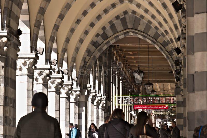 genua Leute gehen unter einen alten Säulengang lizenzfreies stockbild