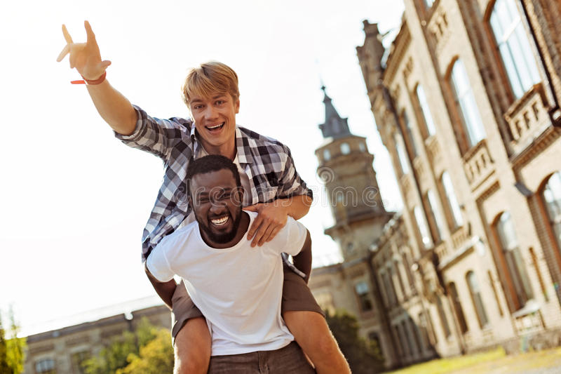 Genuine goofy guy having fun with his friend stock photo