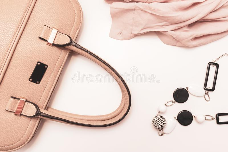 Genuine leather handbag, black and white bijouterie necklace with geometric beads and beige luxury fabric on white background - royalty free stock image