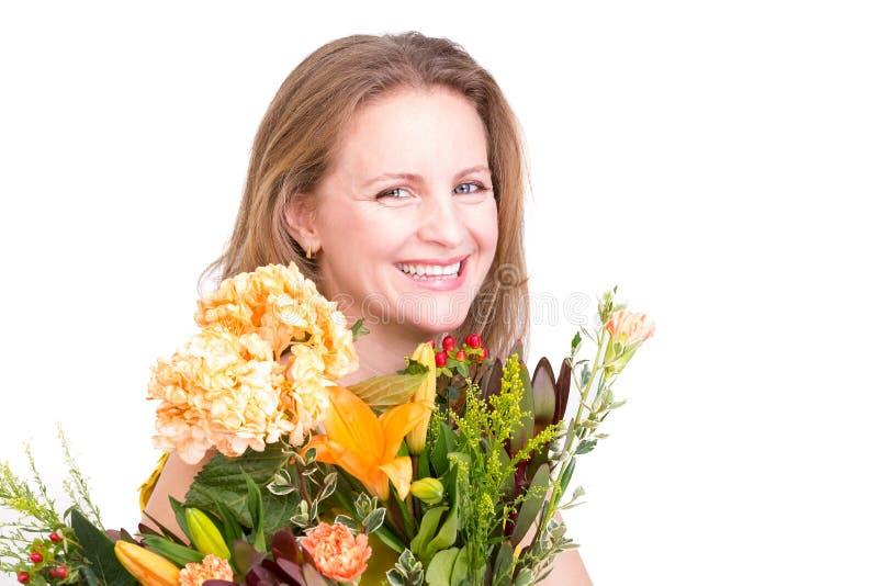 Genuint lycklig kvinna som ler bak blommabuketten royaltyfri fotografi