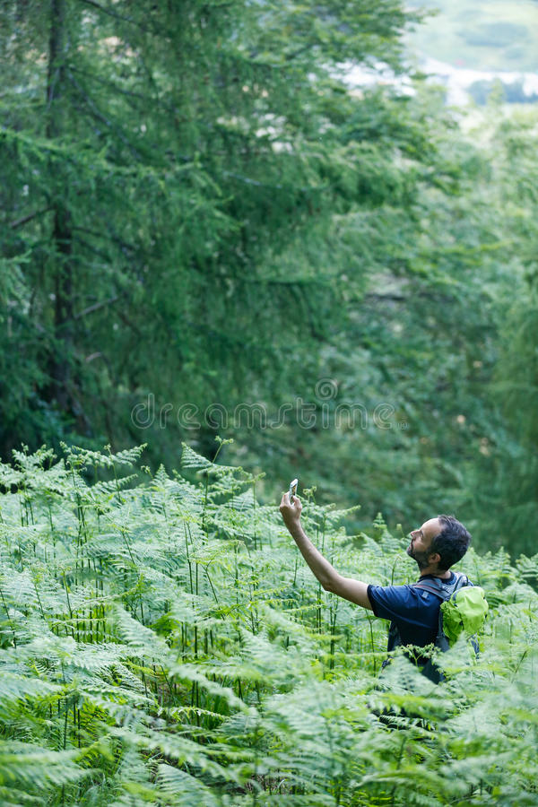 Geocaching. Hiker searching cache using global positioning device stock image