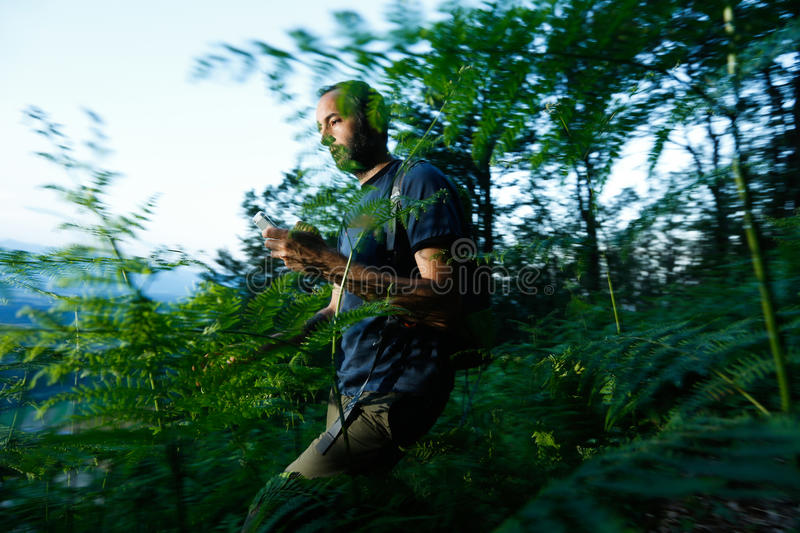 Geocaching. Hiker searching cache using global positioning device royalty free stock images