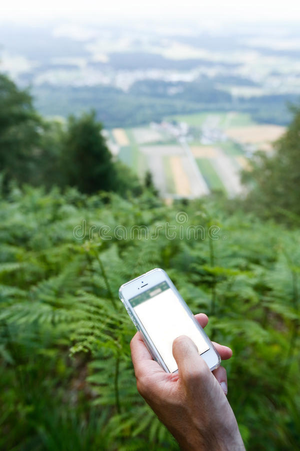 Geocaching. Trekker searching path to cache using mobile device royalty free stock image