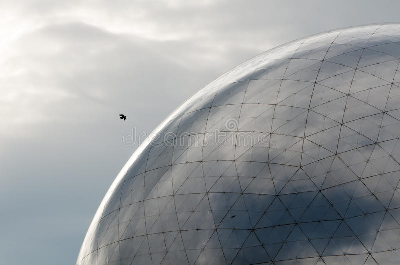 Geodesic dome. Futuristic vision of geodesic dome on grey day with silhouette of bird in the sky. La Geode, City of Sciences Paris La Villette, France stock images