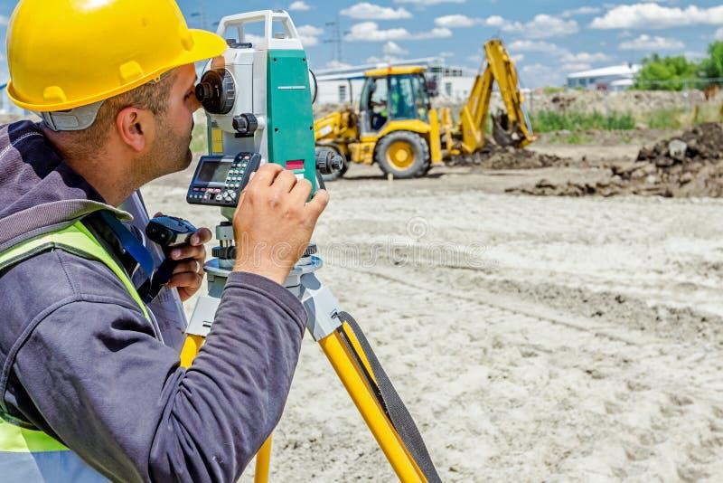 Geodesist работает с полной станцией на строительной площадке Civi стоковые фото