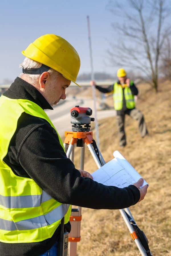 Geodesist a affiché des plans sur le chantier de construction image stock