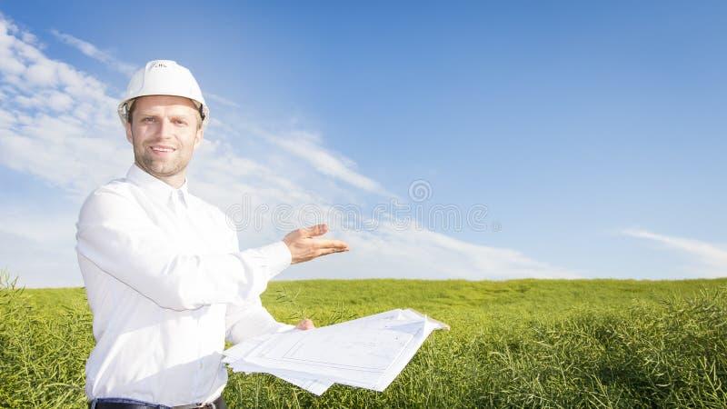 Geodesist com os desenhos na terra para a construção de construção Construtor na documentação branca do capacete e do projeto no  imagens de stock