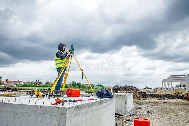Geodesist fonctionne avec la station totale sur un chantier Civi photo libre de droits