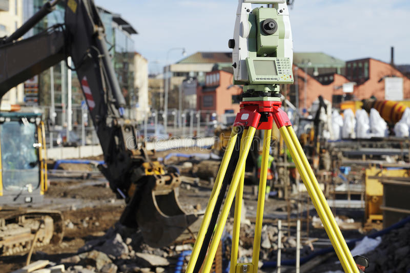 Geodesy total station and construction. Close-ups of large computerised geodesy station, construction works and bulldozers in background royalty free stock photo