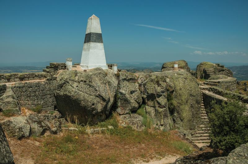 Geodetic pillar on rocky hilltop at the Castle of Monsanto. Geodetic pillar on rocky hilltop with stone walls and countryside landscape, in a sunny day at the royalty free stock photos