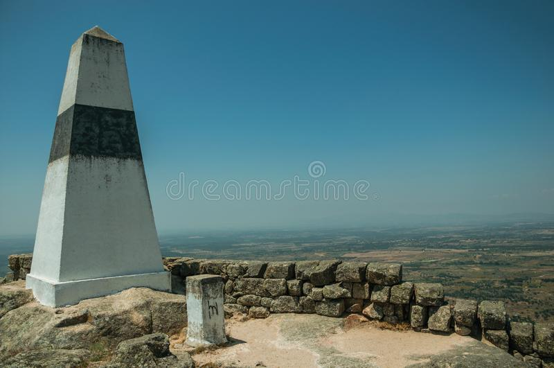 Geodetic pillar on rocky hilltop at the Castle of Monsanto. Geodetic pillar on rocky hilltop with stone walls and countryside landscape, in a sunny day at the royalty free stock image