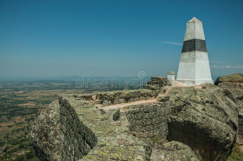 Geodetic pillar on rocky hilltop at the Castle of Monsanto. Geodetic pillar on rocky hilltop with stone walls and countryside landscape, in a sunny day at the royalty free stock images