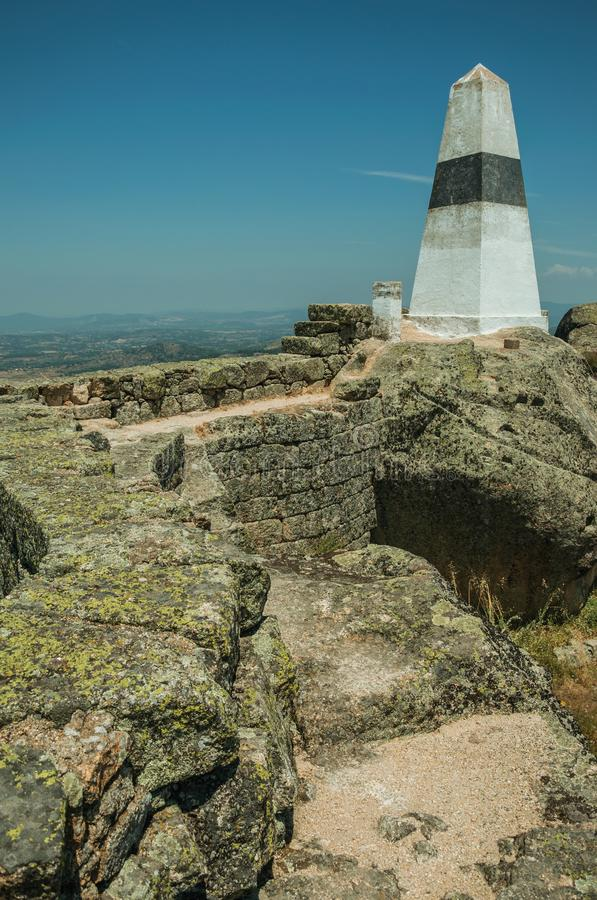 Geodetic pillar on rocky hilltop at the Castle of Monsanto. Geodetic pillar on rocky hilltop with stone walls and countryside landscape, in a sunny day at the stock photo