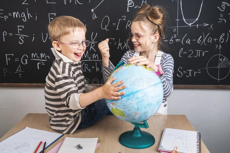 Geography lesson: A boy and a girl are sitting on a desk and studying the globe on the background of a school board. royalty free stock image