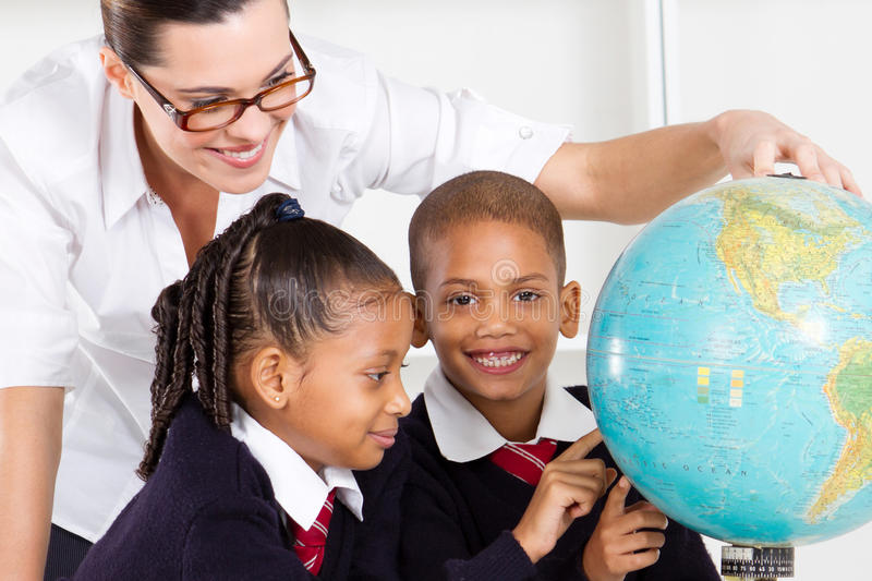 Geography teacher and students. Elementary geography teacher and students looking at globe in classroom royalty free stock photography