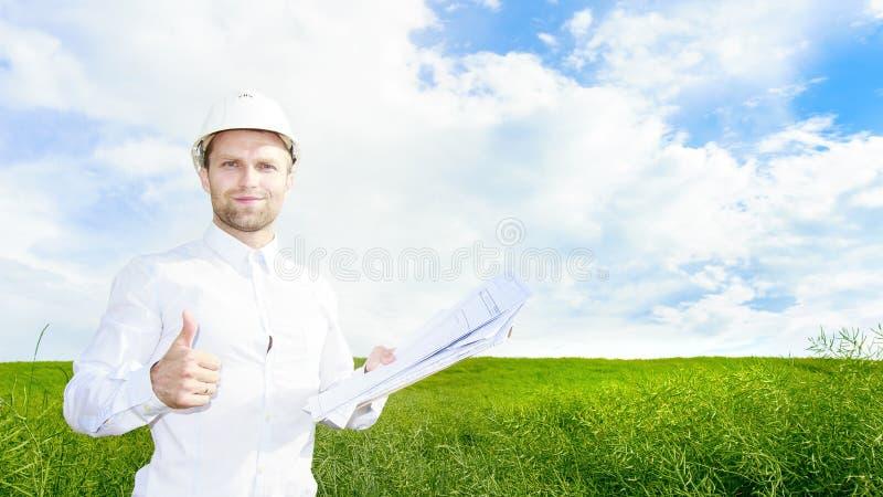 Geologen i den vita hjälmen på grön äng med teckningar i händer rymmer upp hans tumme Teknikerbyggmästare på konstruktionsplats royaltyfria foton