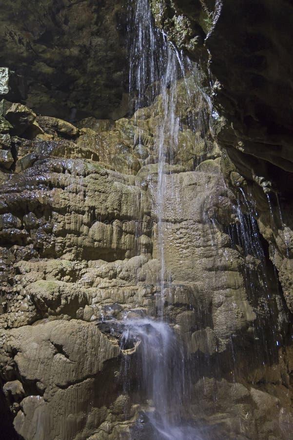 Geologische rotsvormingen en waterval in een ondergronds hol royalty-vrije stock afbeeldingen