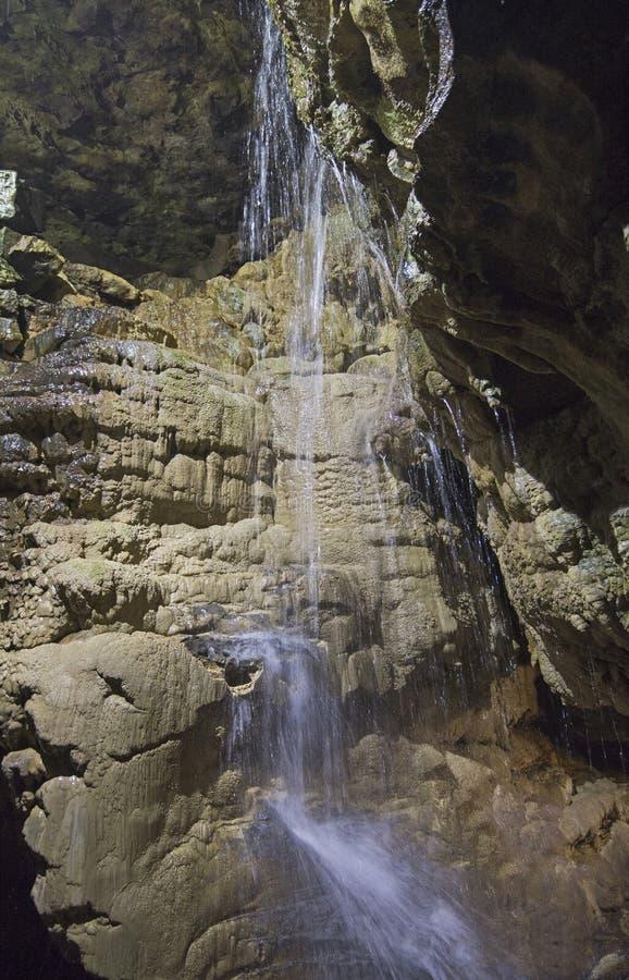 Geologische rotsvormingen en waterval in een ondergronds hol stock fotografie