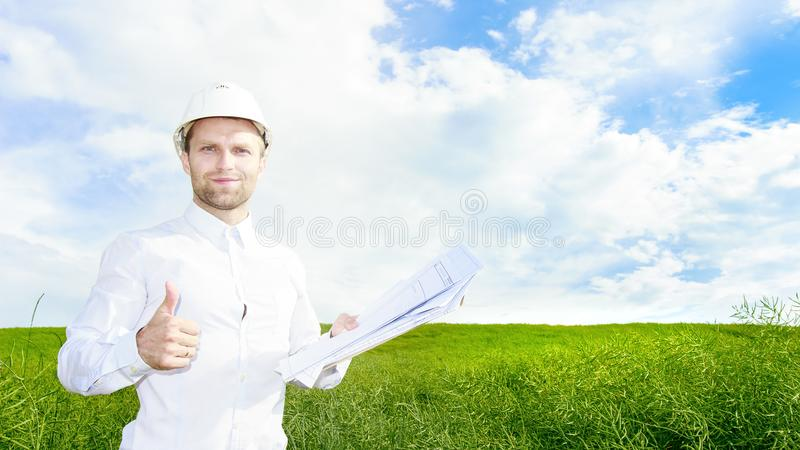 Geologist in white helmet on green meadow with drawings in hands holds his thumb up. Engineer builder on construction site royalty free stock photos