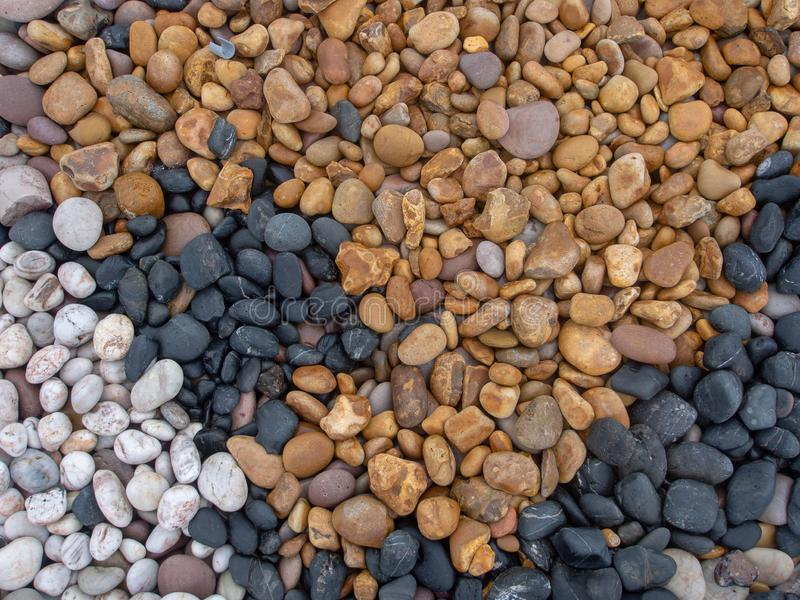 Geology. Sea pebbles on beach, various colors and types of stone. Multicoloured stones - black, white, yellow. stock images