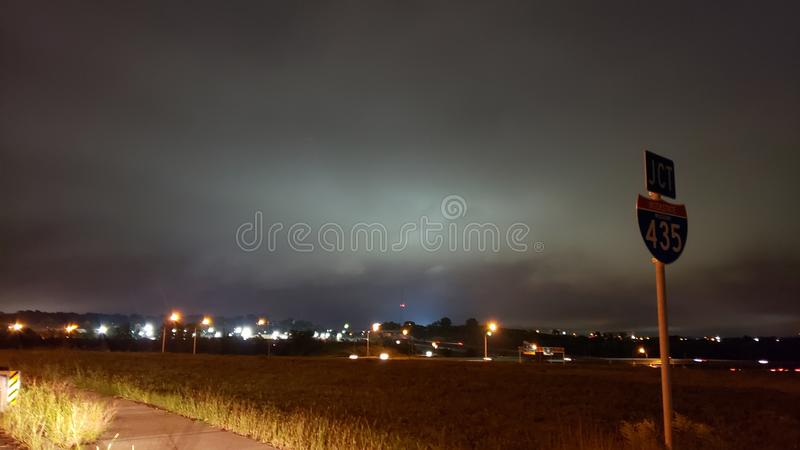Geomagnetic Storm over cityscape. White anomaly behind clouds and Blue slow on ground over Kansas city royalty free stock photography