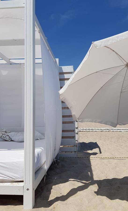 Geometría de la sombrilla y de la sombra blancas del parasol de playa en la arena clara de la playa imagen de archivo libre de regalías