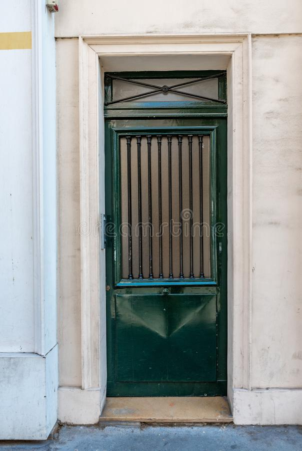 Geometria antykwarska drzwiowa kratownica z okrzesaną powierzchnią malował w głębokim - zielony kolor Fasada stary budynek w Pary zdjęcie royalty free