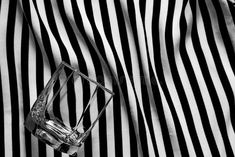 Geometric black and white background with a glass of old fashioned stock photography