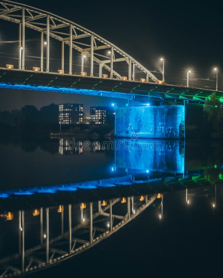 Geometric blue bridge to another world. Night scene of blue-highlighted bridge with residential blocks in background below him and reflection of them in the