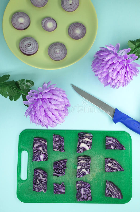 Geometric composition of cabbage, onions, flowers with a knife royalty free stock photos