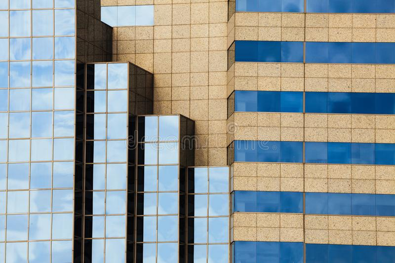 Geometric facade glass windows with sky reflected. And architecture of a modern office building, construction background. Corporate center royalty free stock images