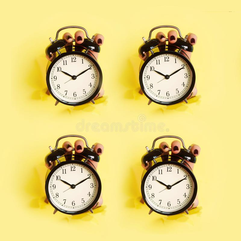Geometric pattern of hands holding black alarm clock through hole in yellow paper background. Wake up alert concept. Morning royalty free stock photos