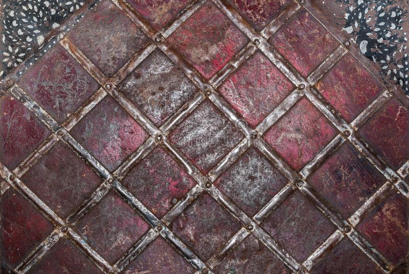 Geometric pattern of tin strips nailed to rusty metal sheet, painted in red and black sheets in top corners . Metal grunge background. Geometric pattern of tin stock photo