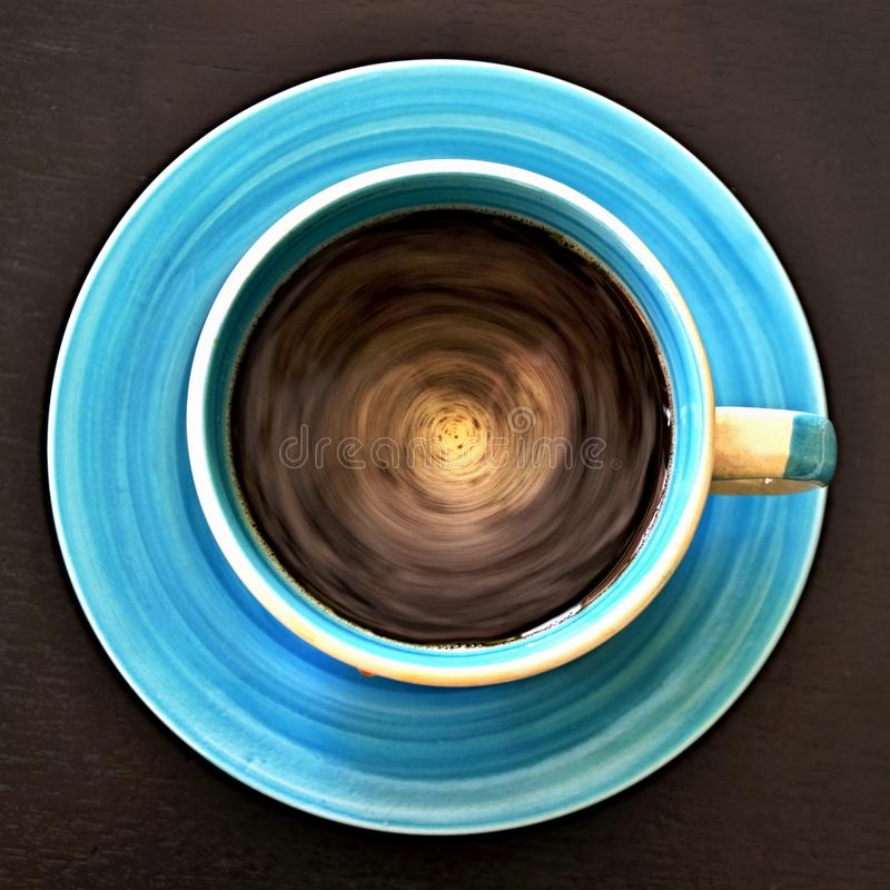Geometric patterns - top view of the circulating coffee in a circular cup. Hot coffee still circulating after thorough stirring, the blue cup is decorated with stock photos