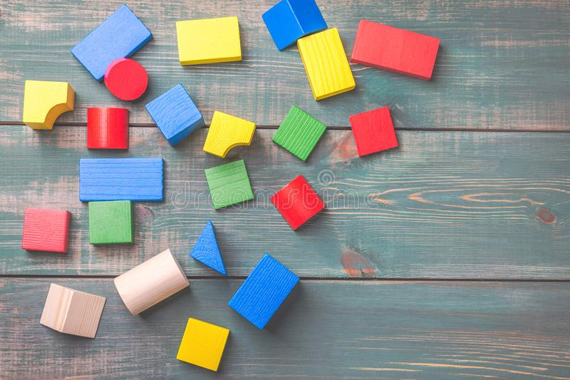 Geometric shapes for kids logical thinking. Colorful wooden blocks on green wooden background. Children`s building blocks. royalty free stock photography