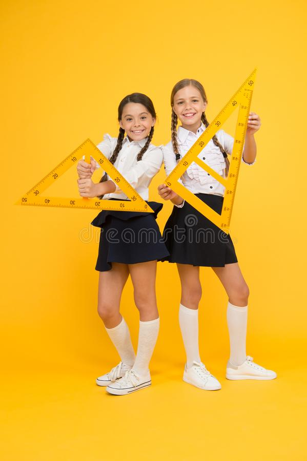 Geometric shapes. pupils use gon ruler. stem disciplines. back to school. Maths and geometry. Kids in uniform at yellow stock photo