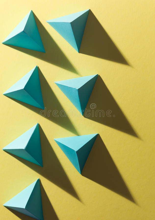 Geometric study. Blue paper pyramids with harsh shadow on yellow background stock photography