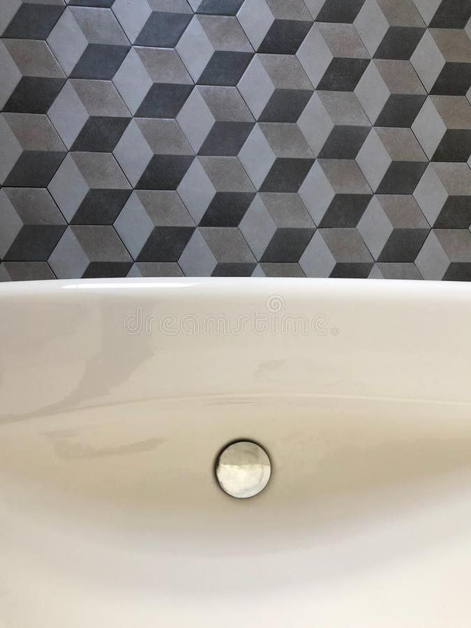 Geometric tiles and white washbasin for vintage bathroom. Geometric tiles pattern and white ceramic washbasin for vintage bathroom royalty free stock photos