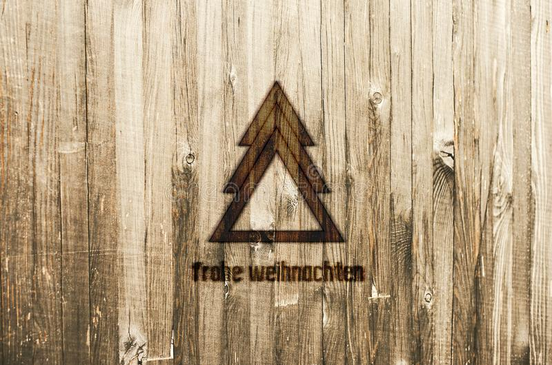 Geometrical Christmas Tree Burned in Wood. Christmas Card with text in German Frohe Weihnachten, in English Merry Christmas. Geometrical Christmas Tree Burned stock images