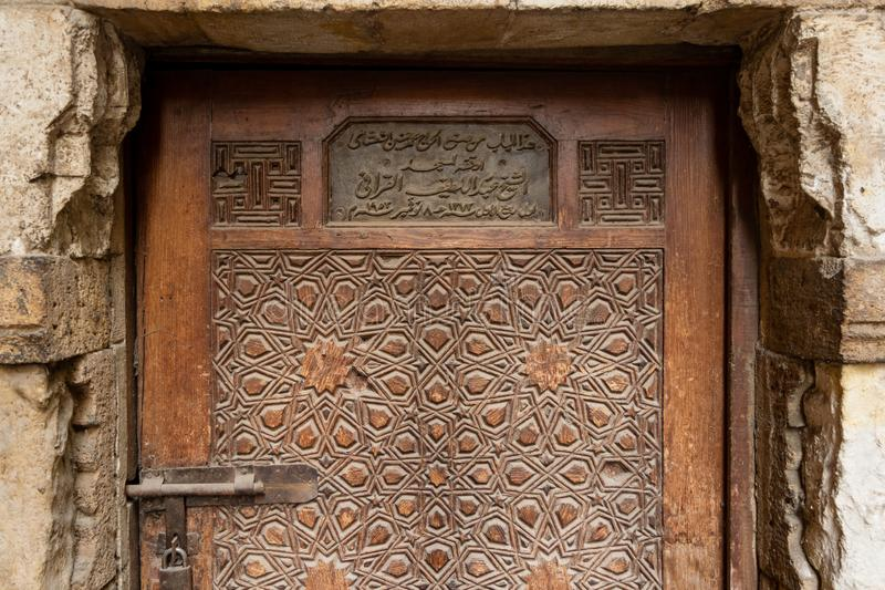 Aged wooden engraved door of El Korafi historic mosque, signed by the maker, Cairo, Egypt. Geometrical engraved decorations of an aged wooden ornate door of Abd royalty free stock photos