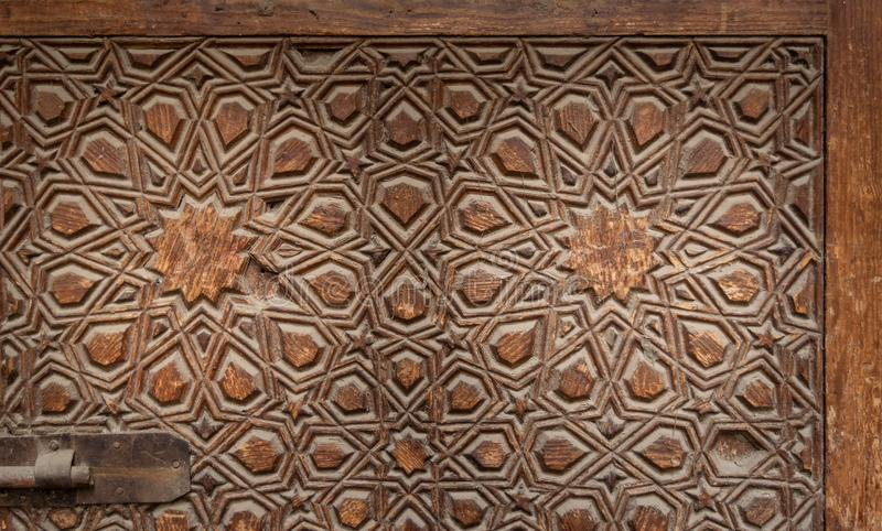 Geometrical engraved decorations of an aged wooden ornate door leaf. Old Cairo, Egypt royalty free stock images